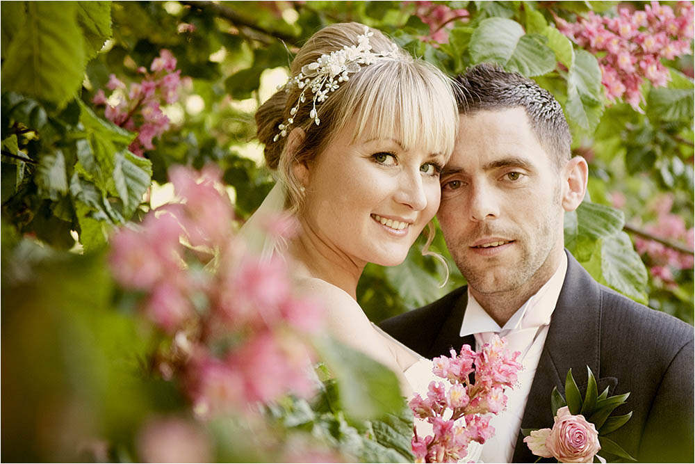 Young couple in wedding dress and suit with a tree in blossom.  Photography Copyright © Mick House, All Rights Reserved