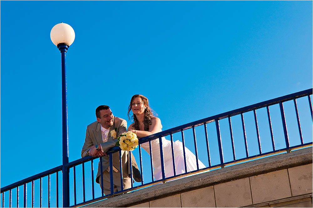 Bride and groom leaning over a railing at Eastbourne Bandstand.  Photography Copyright © Mick House, All Rights Reserved
