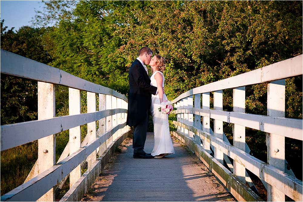 Bride and groom kissing on the bridge at Alfriston.  Photography Copyright © Mick House, All Rights Reserved