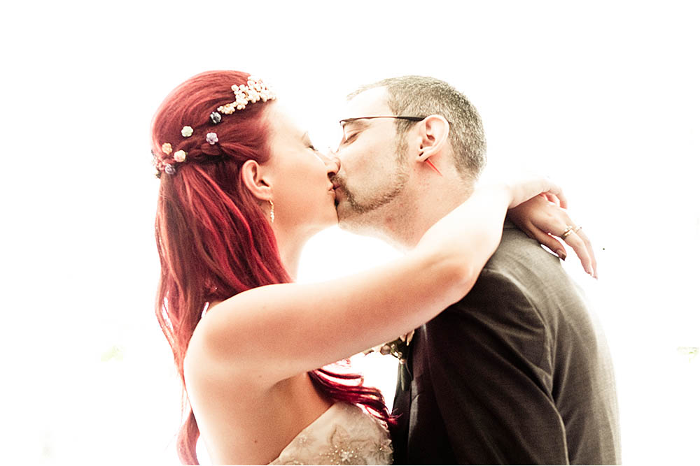 Bride and groom kissing against a white background.  Photography Copyright © Mick House, All Rights Reserved