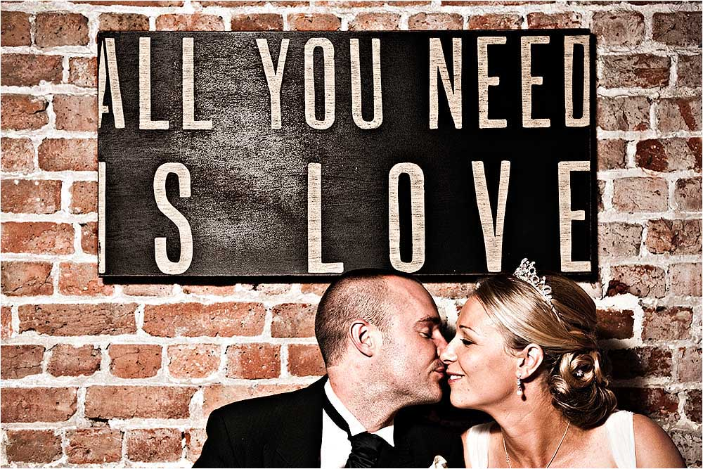 Young couple kissing under a sign.  Photography Copyright © Mick House, All Rights Reserved