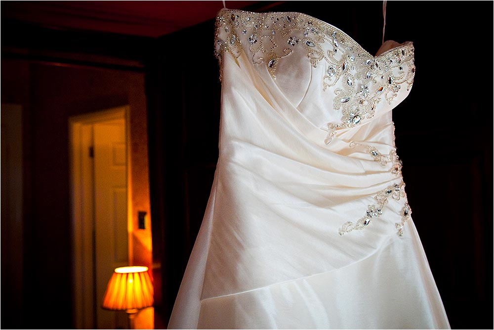 A lovely wedding dress hanging with a lamp behind.  Photography Copyright © Mick House, All Rights Reserved