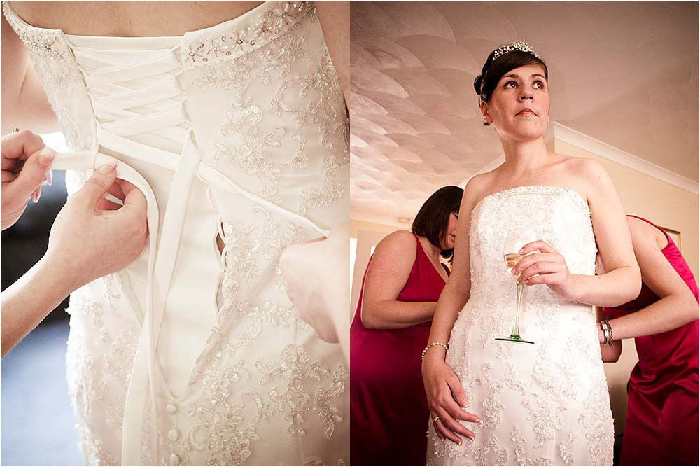 Bride drinking champagne and detail of the dress being laced