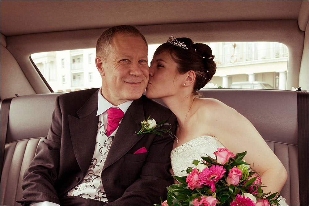 Suzanne giving her dad a kiss in the back of the car