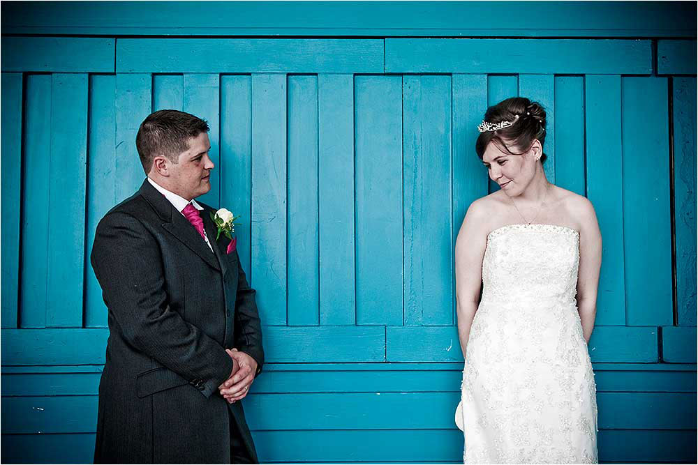 Bride and Groom standing against a blue wooden wall