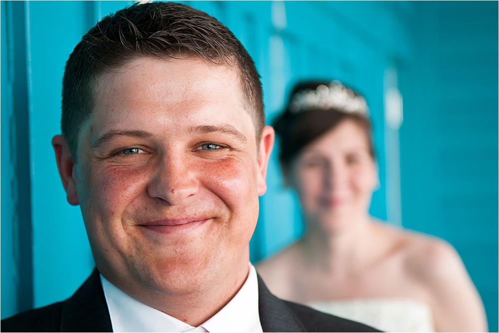 Short depth of field photograph of the groom with the bride in the background