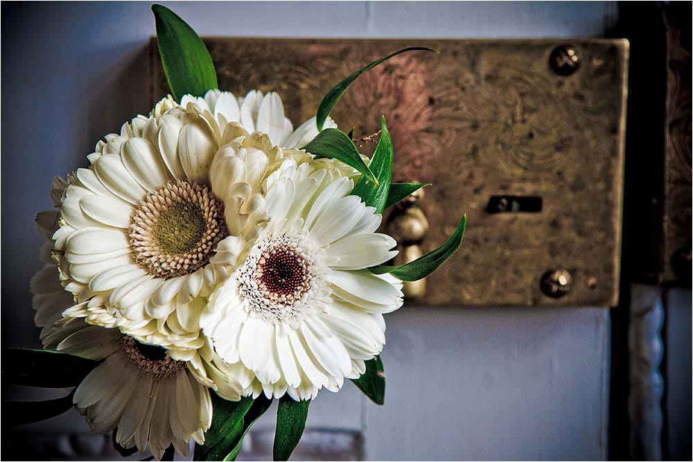 Detail of ivory flowers against a brass door plate