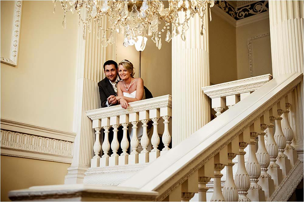 Image of the couple looking down from the ornate stairwell balcony