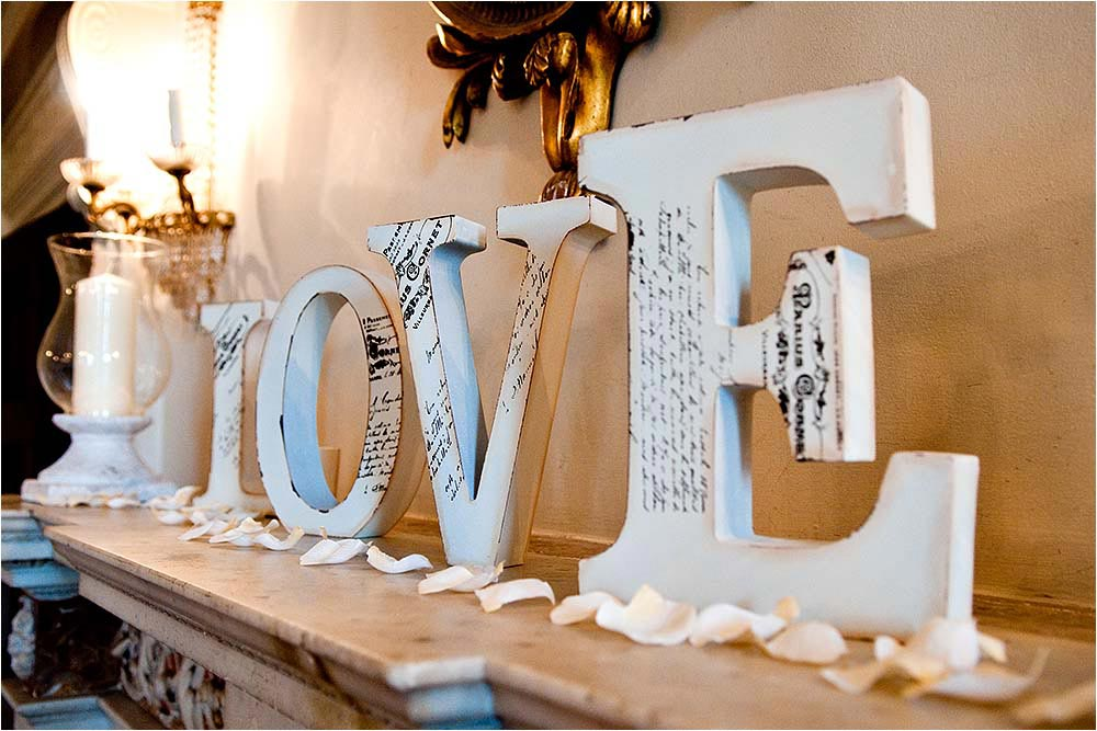 Carved woodin letters spelling out the word Love on a fireplace