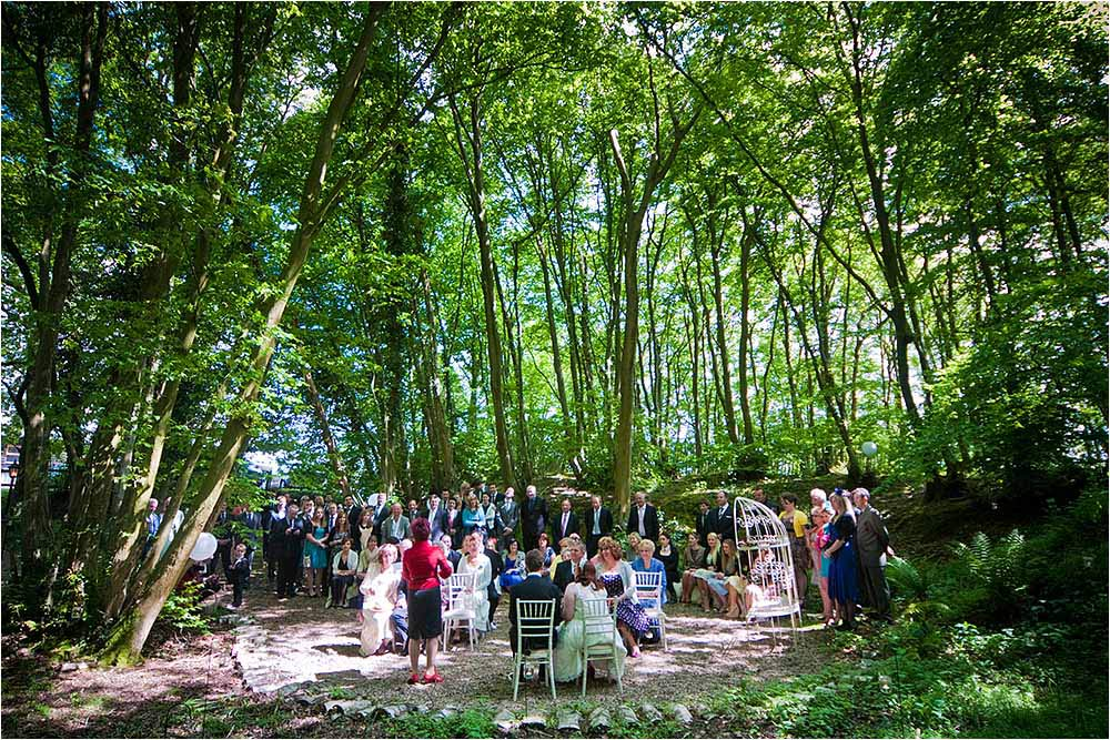 The wedding ceremony taking place in the woods at Swallows Oast