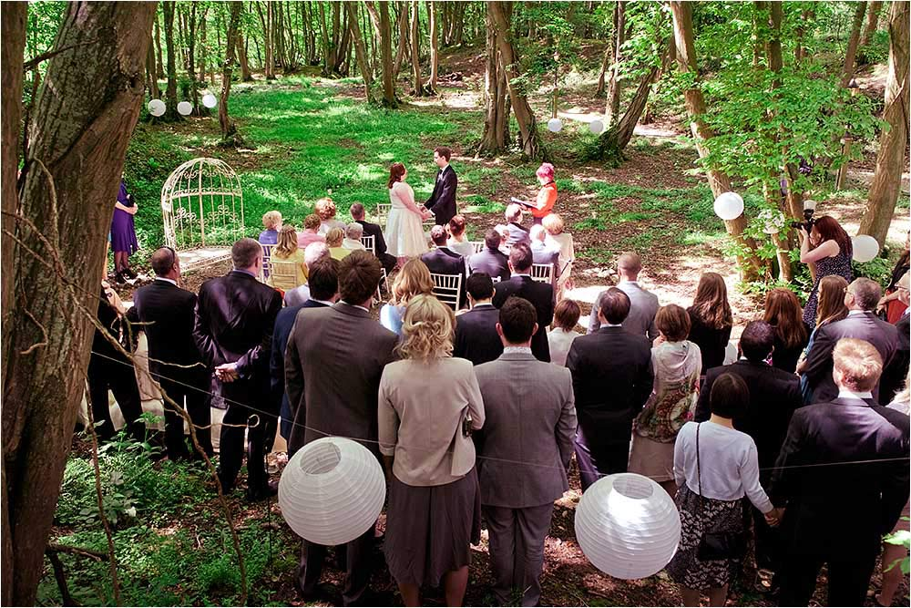 Guests watching the ceremony seen from a small hill in the woods