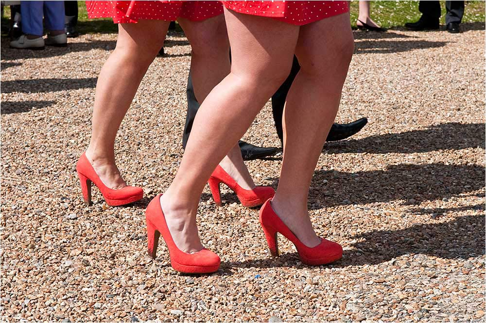 Two pairs of bridesmaids legs with orange shoes