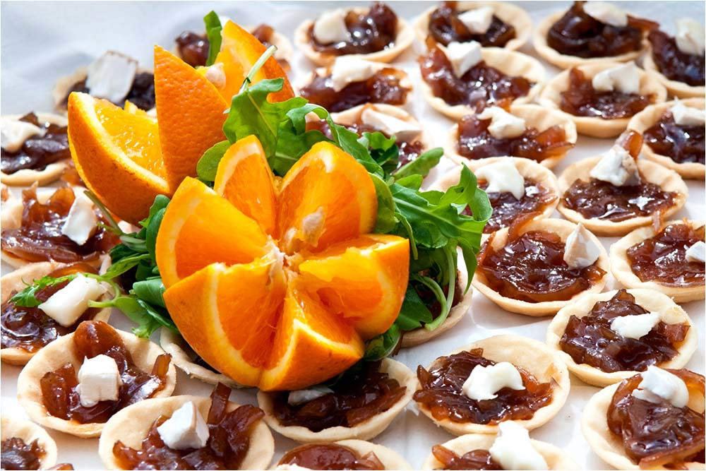 A tray of canapes with sliced oranges