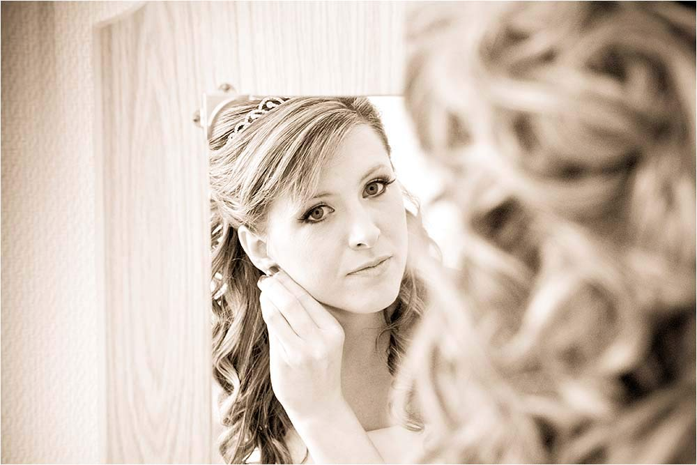 The bride putting on earings while looking in the mirror