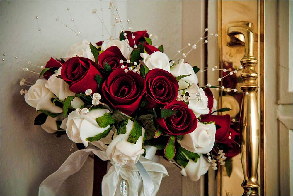 A red and white rose bouquet standing beside a brass door plate