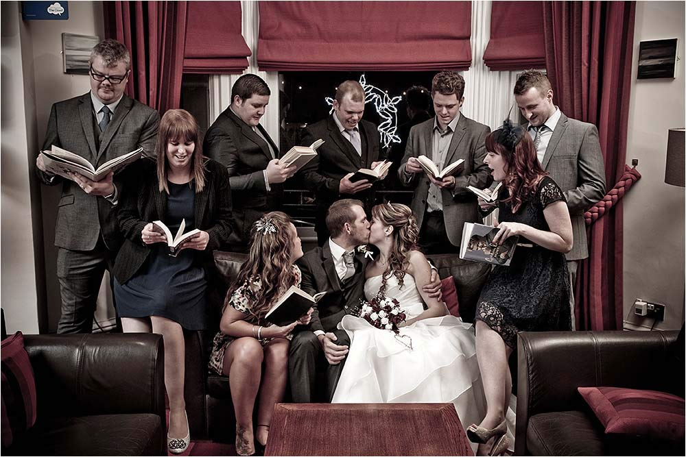 Amusing group image of the guests reading and the bride and groom kissing
